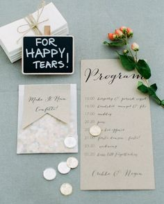 """The programs, printed on recycled brown paper like the invitations, gave a trilingual timeline schedule of the day. Guests also received confetti to sprinkle on the couple during the recessional; Negin conceived the idea of the """"Make It Rain Confetti"""" sign that topped the bags, and then enlisted SepiaSmiles to make the cute detail. Tissues were on hand for emotional moments during the ceremony, and the resourceful bride found the idea for the accompanying """"For Happy Tears"""" poster…"""