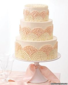 Perhaps the most classic of cake finishes, buttercream always looks (and tastes) luscious. Here, Ohio baker and Weddings contributing editor Wendy Kromer covered each tier of the cake in Swiss meringue buttercream, then created a repeated flourish with a petal tip, which gives the cake a modern style. Half-circles traced on each tier provided a guide for piping the fan shapes, done in plain and pink-tinted buttercream. This design relies on a single pastry tip, but because bakers have a…