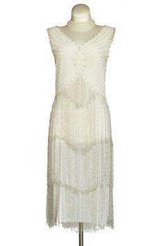 1920s Style White Diamond Flapper Dress - This is an amazing reproduction flapper dress that is simply stunning. It is all hand beaded in glass beads, with a gorgeous beaded fringe. The overall color is ivory with silver beaded fringe.