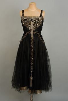 JEWELED and EMBROIDERED SILK and NET DANCE DRESS, c. 1915. Black on black, the sleeveless bodice top trimmed in gold lame and decorated with gold metallic embroidered foliage, clusters of paste jewels and crystal beads, with crystal bead and paste tassels, a single tasseled band continues down skirt front, skirt hem of gold lame, waistband drops to trim panniers on hips.
