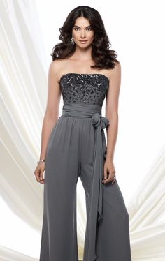Surprise the crowd in Mon Cheri Montage 115976. This unique outfit features a strapless neckline. The top is embellished with dazzling beads and crystals, making this lovely piece even more glamorous and fashionable. The fitted waist is cinched with a ruched fabric and ties at hip, that leads the stunning side drape. The stunning jumpsuit gives a twist to classic elegance.