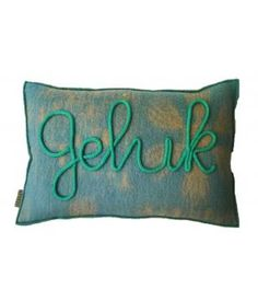 Kussen bekleed met retro wollen dekens en aan de voorzijde het woord GELUK in gepunnikte letters. De kussenhoes sluit met een knoop aan de achterzijde. Inclusief nieuw binnenkussen