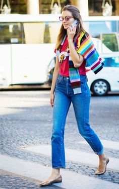 Andreea Diaconu adds some color to her look with a red graphic tee and rainbow striped sweater.