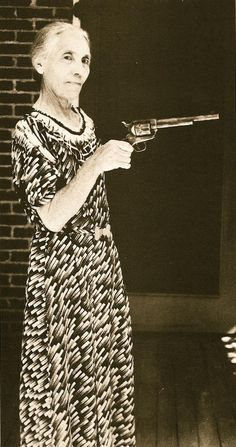 Ms. Apolinaria Gutierrez Garrett, wife of famous frontier sheriff Pat Garrett, holding the gun he used in 1881 to kill Billy the Kid.  Photo circa 1920.
