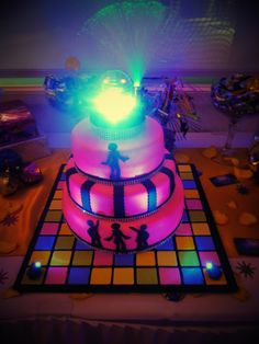 70's Disco Party Cake - Fondant cake, dance floor and dancers are fondant. The top is a spinning disco ball with led lights (purchased at Party City) and two led light on dance floor.