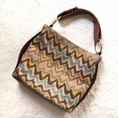 """Big Buddha Winnie Hobo Eye-catching zigzag pattern shoulder bag in brown, turquoise, brown and tan fabric. Rich brown trim and gold tone hardware. Zipper closure with inside zippered pocket. Body: 50% linen; 50% cotton. Trim: 65% polyurethane; 35% cotton. Lining: 100% polyester. 13""""x14""""x5"""".  Adjustable strap from 6.25"""" to 7.75"""". *One buckle fastener is darker than the other but is original. Couple of minor marks on inside due to light use. Very Good Condition. Thanks for looking! Big Buddha…"""
