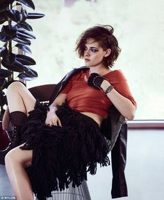 On the fringe: Kristen donned a black fringe skirt and orange knit crop top with lace-up boots for another inside magazine shot