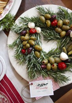 Talk about elevating a simple hors d'oeuvre to a whole new level –  The wreath is made of rosemary, and a variety of olives, tiny pickles, and mozzarella balls were arranged on top.