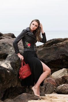 Model Wears Rosie Biker Leather Jacket, Size 8 with painted floral design in Black. Model is holding the Mini Ester Bag in Red