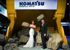 Newly married couple Jesse Townsend and Mariana Balashova hoist boulders for fun in a Komatsu loader truck during the MINExpo International 2016 at the Convention Center on Tuesday Sept. 27 2016.  Townsend is an employee of Komatsu America Corp. and proposed the idea as a fun alternative.