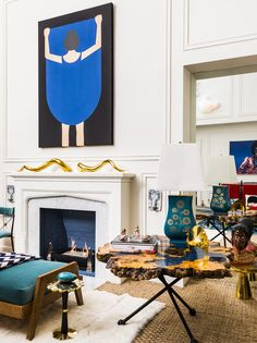 A painting above a sculptural-topped fireplace mantel in a contemporary living space.