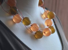 One of my most popular designs. I finally found a creative way to recycle telephone wire! Lovely earthy shades of amber and pale apricot/orange on orange telephone wire.  By J Sadler Designs.