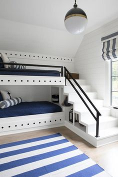 A nautical style white built-in bunk bed is dressed in blue bedding accented with blue and white pillows and gray striped lumbar pillows.
