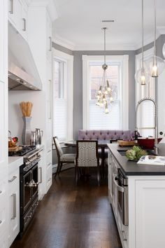 Incredible kitchen features bay window breakfast nook lit by an glass cluster pendant over a oval dining table lined with white and gray geometric dining chairs and a purple tufted banquette bench against a backdrop of gray walls. The kitchen boasts white shaker cabinets paired with brushed nickel hardware and white marble counters which frame a black range opposite a large island.