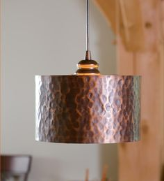 copper kitchen pendant lights of drum lamp shades on hammered metal finish across wood indoor columns alongside high back wooden dining chairs
