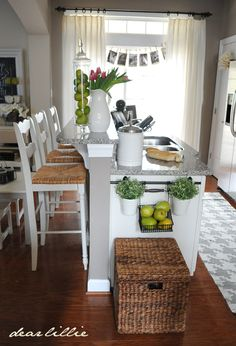 Tons of pics of two different kitchens. Love the black and white photos in the window