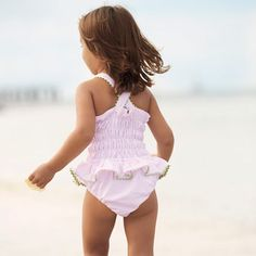 Guaranteed to turn heads with its sassy pleated ruffle skirt and elasticized ruching at the back. Straps criss cross and button in back. Fully lined. 100% cotton; machine wash. Pink Seersucker. Sizes 6m-6y (sizes 6-24m have snap closures at the legs).