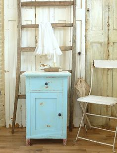 The wall is covered with old doors and shutters in an old worn white paint.. ....great back drop for furniture....