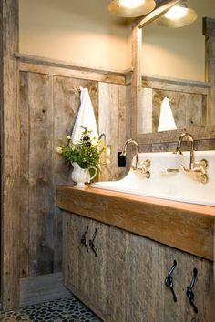 Rustikale Holzschränke und glanzvolle Wascharmatur für Badezimmer kunstvoll geschwungen