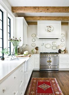 This kitchen is EVERYTHING! Light, bright & airy, while retaining original windows. An open wall with white paneling backsplash is decorated with hanging platters. Crown moulding, brackets and bead board give cabinets the feel of furniture while the beams add character.