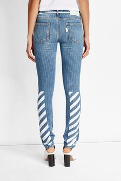 Classically slim, these jeans from Off-White are taken straight off of the SS '17 runway. Made distinct with the diagonal stripes at the calves, the thin pinstripes create a sleek look while the string belt adds sporty and offbeat character #promotion