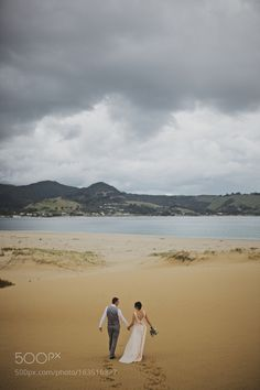 Bridal couple walking hand in hand at the Hokianga sand dune. by GregCampbellWeddingPhotography