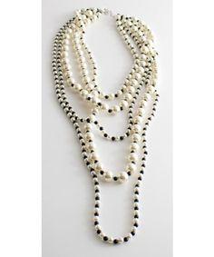Maxi collana di perle sintetiche con allacciatura tramite gancetto in metallo.