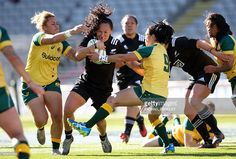 New Zealand's Portia Woodman (C) breaks the tackle from Australia's Hanna Sio (L) and Iliseva Batibasaga (R) during the women's rugby test match between the New Zealand Black Ferns and Australia at Eden Park on October 22, 2016. / AFP / MICHAEL