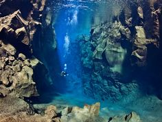 A diver swimming between two tectonic plates in Iceland