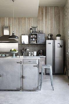 Une cuisine de campagne avec des meubles métallisés. Au centre, un comptoir de boucher gris.