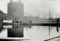 "Experimental motor boat 'Duchess' at Brentford on the Grand Junction Canal. Black and white photograph of 'Duchess' with ""Thornycroft Gas Motor"" written on the side. The boat is a gas powered suction producer, and an ex Fellows, Morton & Clayton Limited steamer. There are men on the boat and industrial buildings in the background. Date: January 1906. #London #canal #Boat #Brentford #grand #union #fellows #morton #clayton #thorneycroft #gas"
