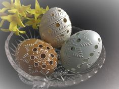 This is a set of three real eggs: 1 chicken eggs in its natural white, 1 chicken in brown, and 1 duck egg in blue. They are decorated using only white wax. Each of them has round holes drilled into its eggshell, and its white wax-embossed design is similar to the delicacy of lace. Creating