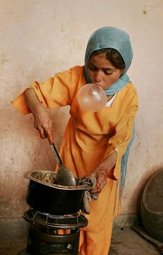 An Afghan girl blows a bubble while she cooks for her family.