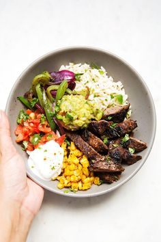 Steak fajita bowls made with garlic lime rice. These bowls are just like chipotle but actually better! The steak is marinated in my easy homemade marinade.