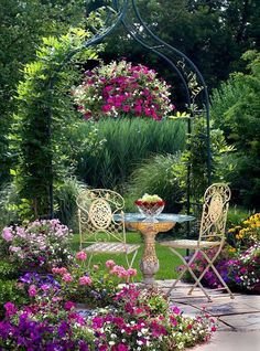 Lovely arbor, hanging basket, and seating amongst flowers - beautiful.