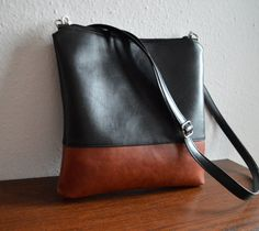 This cross-body / shoulder bag is handmade of two tone distressed faux leather.    Perfect everyday bag.    Closes with a zipper. The interior is fully