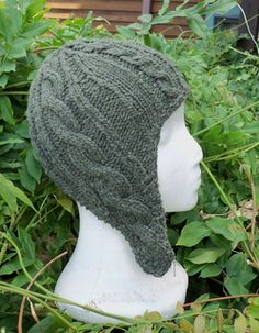 This cabled earflap hat is worked from the bottoms of the flaps up. The two earflaps are worked separately, back and forth, then joined in the round, with the rest of the hat cast on. The whole hat is symmetrical in a way that's nonobvious from the front but still cuts the number of instructions in half.