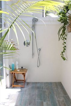 This is an outdoor shower, but you could easy put a little teak table in your shower for bath stuff and add a couple plants for dimension and softness.