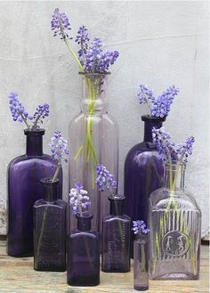colored flowers in same colored antique glass bottles.  what a great impact!