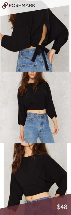 Black Dolman Crop Top This black crop top features a semi loose silhouette on top but tight at the waist, dolman sleeves, and cross over design at the back. Back buttons and tie closures. So insanely hot with high waisted black leather pants or distressed denim. Polyester. Haoduoyi label. Nasty Gal Tops Crop Tops