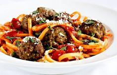 V troubě grilované masové kuličky, servírované s těstovinami přelitými prohřátou omáčkou Dolmio Bolognese, porce ozdobené strouhaným parmezánem a tymiánem.