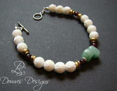 """take an adventure with this bracelet. Aventurine, Garnet and Clam Shell carved beads are spaced with brass and sterling silver roundels with toggle clasp. 7 3/4"""" in length"""