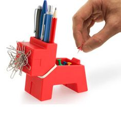 The Rocky Desk Butler - Desktop Organizer is a fun and playful desk organizer in the shape of a dog. He has a magnetic mouth for paper clips, he holds pens and pencils, he has easy storage for rubber bands around his neck and a small storage space on his back. $18.95