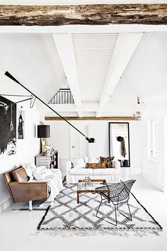 White living space, beams, vaulted ceiling, Flos wall lights, vintage Moroccan rug