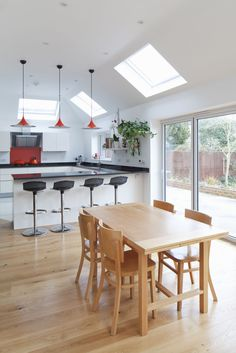 Modern kitchen extension | breakfast bar stools | u shaped kitchen layout | vaulted ceiling | velux rooflight | open plan kitchen dining | dual pitch roof | feature pendant lighting