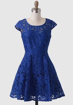 This stunning blue fit-and-flare dress features a sheer organza overlay with intricate floral embroidery allover and a keyhole slit at the back.