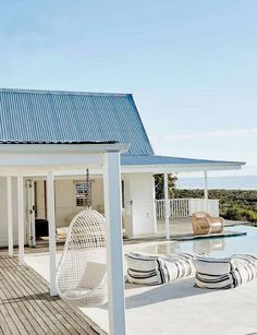 Situated in South Africa's Grotto Bay, a whitewashed beach house of a minimalist feel emulates the serene simplicity of its surround. Its backdrop, miles of fluctuating shades of ocean blues, establish a tonal contrast against the stark exterior of the home.