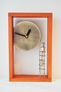 Bronze clock in an orange wooden frame with bronze ladder and two figures  ascending. $92.50, via Etsy.