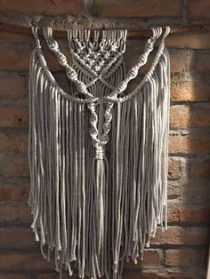 A large, light gray macrame hanging for the wall. Its size is 80 cm (height) by 40 cm (width), the length of the pole which it hangs on is 70 cm (it can be shortened). It is made of cotton string.