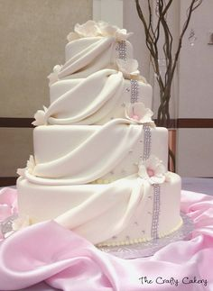 Draped fondant wedding cake with white flowers and rhinestone accents
